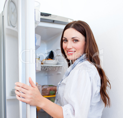 Happy woman looking for something in the fridge