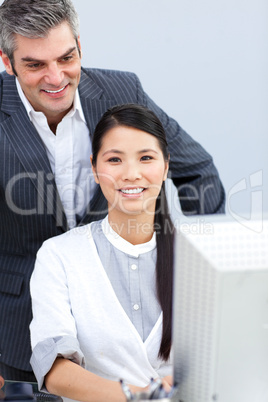 Asian businesswoman and her manager working at a computer