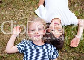 Adorable siblings lying on the grass