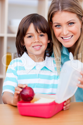 Cheerful little boy and his mother preparing his snack