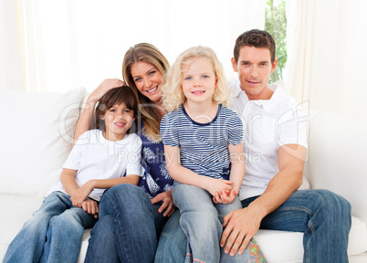 Joyful family watching television sitting on sofa