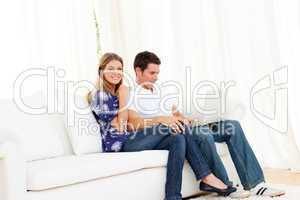 Jolly couple using a laptop sitting on sofa