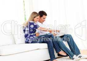 Merry couple using a laptop sitting on sofa