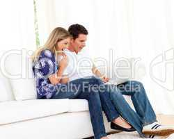 Cheerful couple using a laptop sitting on sofa