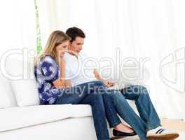 Romantic couple using a laptop sitting on sofa