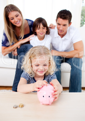 Smiling little girl inserting coin in a piggybank