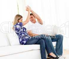 Lively couple using a laptop sitting on sofa