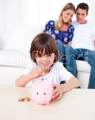 Joyful little boy inserting coin in a piggybank in the living ro