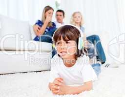 Smiling little boy listening music lying on floor