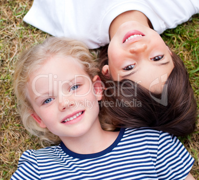 Close-up of cute siblings lying on the grass
