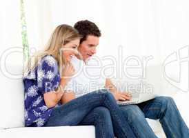 Animated couple using a laptop sitting on sofa