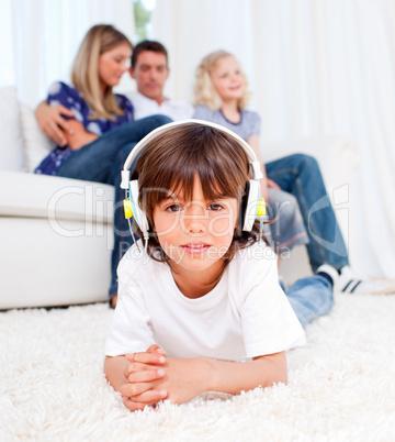 Cute little boy listening music lying on floor