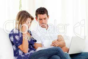 Distressed couple angry with so many bills to pay
