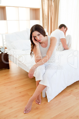 Angry couple sitting separately on their bed