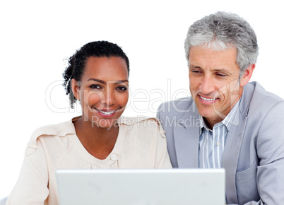 Multi-ethnic business co-workers using a laptop