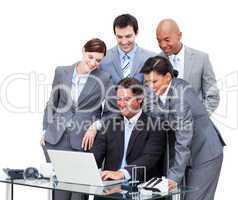Cheerful international business team looking at a laptop