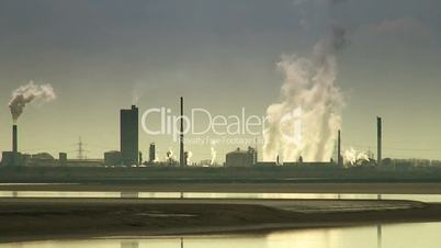 Smoke pouring from chimneys of petrochemical plant