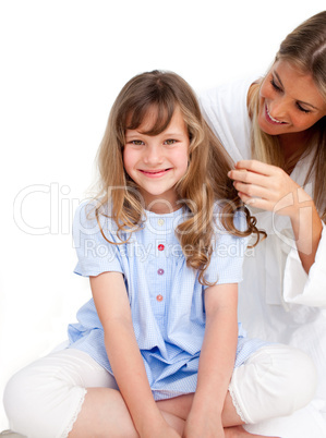 Pretty woman brushing her daugther's hair