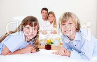 Jolly family having breakfast sitting on bed