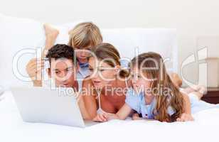 Merry family buying online lying down on bed