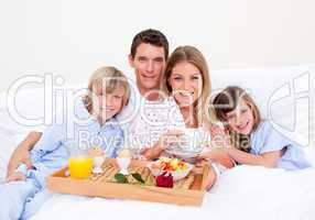 Smiling family having breakfast sitting on bed