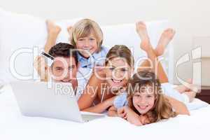 Enthusiastic family buying online lying down on bed