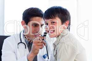 Concentrated doctor examining little boy's ears