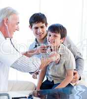 Positive doctor examining a little boy with his father