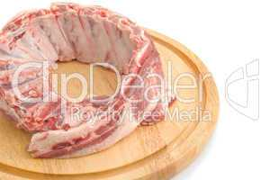 Uncooked Pork ribs on round hardboard
