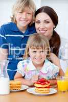 Portrait of a mother and her children having breakfast