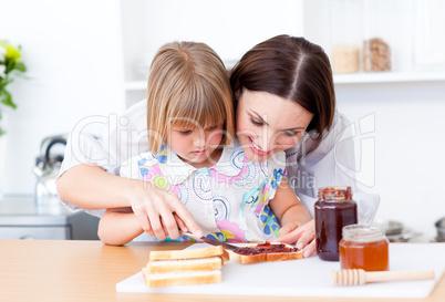 Brunette mother helping her daughter prepare the breakfast