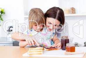 Brunette mother helping her daughter prepare the breakfast