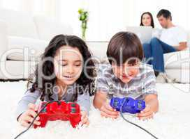 Cute siblings playing video games laying down on the floor