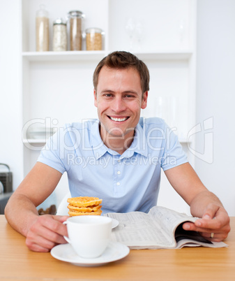 Handsome man reading newspaper during the breakfast