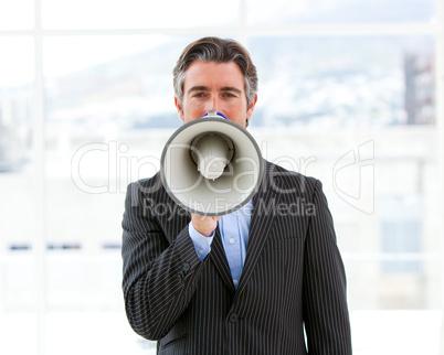 Mature businessman yelling through a megaphone