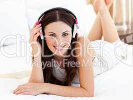 Charming woman lying down on bed listening music