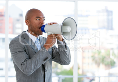 Ambitious businessman yelling through a megaphone