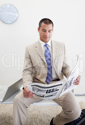Confident manager reading a newspaper
