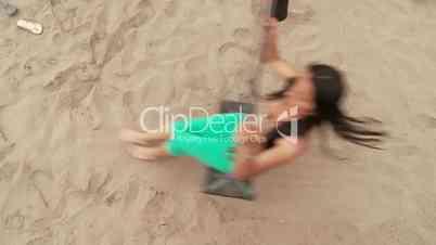 Frau schaukelt am Strand