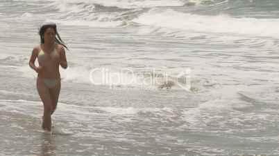 Frau im Bikini joggt am Strand