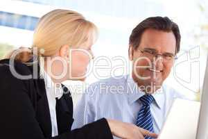 Businessman and Female Colleague Using Loptop Outdoors
