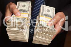 Businessman Handing Over Stacks of Money