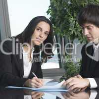 Junge Geschäftsfrau unterschreibt Unterlagen