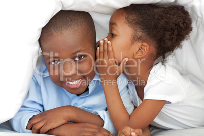 Cute little girl whispering something to her brother