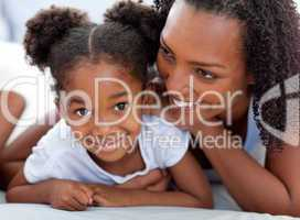 Attentive woman and her daughter relaxing lying down on bed