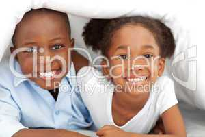 Portrait of ethnic siblings lying down on bed