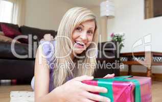 Joyful young woman holding presents lying on the floor