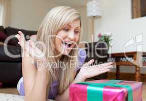 Surprised young woman opening gifts lying on the floor