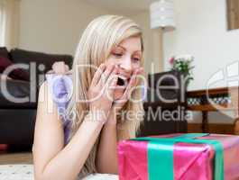 Surprised woman opening gifts lying on the floor