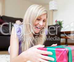 Cheerful young woman holding presents lying on the floor